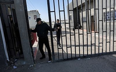 A Palestinian security man closes the gate of the Kerem Shalom crossing, the main passage point for goods entering Gaza, after it was closed by Israel following the discovery of smuggling tunnels underneath the crossing, in the southern Gaza Strip town of Rafah on January 14, 2018. (AFP PHOTO / SAID KHATIB)