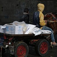A Palestinian youth rides a horse-pulled cart with food donations outside the United Nations food distribution center in Gaza City on January 15, 2018 (AFP PHOTO / MOHAMMED ABED)