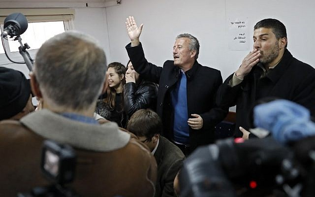 Bassem Tamimi (C) the father of sixteen-year-old Palestinian Ahed Tamimi (UNSEEN), a well-known campaigner against Israel's occupation, waves at his daughter during a hearing in the Israeli military court at Ofer military prison in the West Bank village of Betunia on January 15, 2018. (Thomas Coex/AFP)