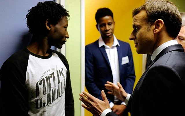 French President Emmanuel Macron speaks to Ahmed Adam (L) from Sudan during his visit to a migrant center in Croisilles, northern France, on January 16, 2018. (Michel Spingler/AFP)