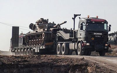 A photo made available by the Dogan New Agency shows Turkish army military trucks transporting armored vehicles to reinforce the border units close to the Syrian border on January 16, 2018. (AFP PHOTO / DHA / DHA)