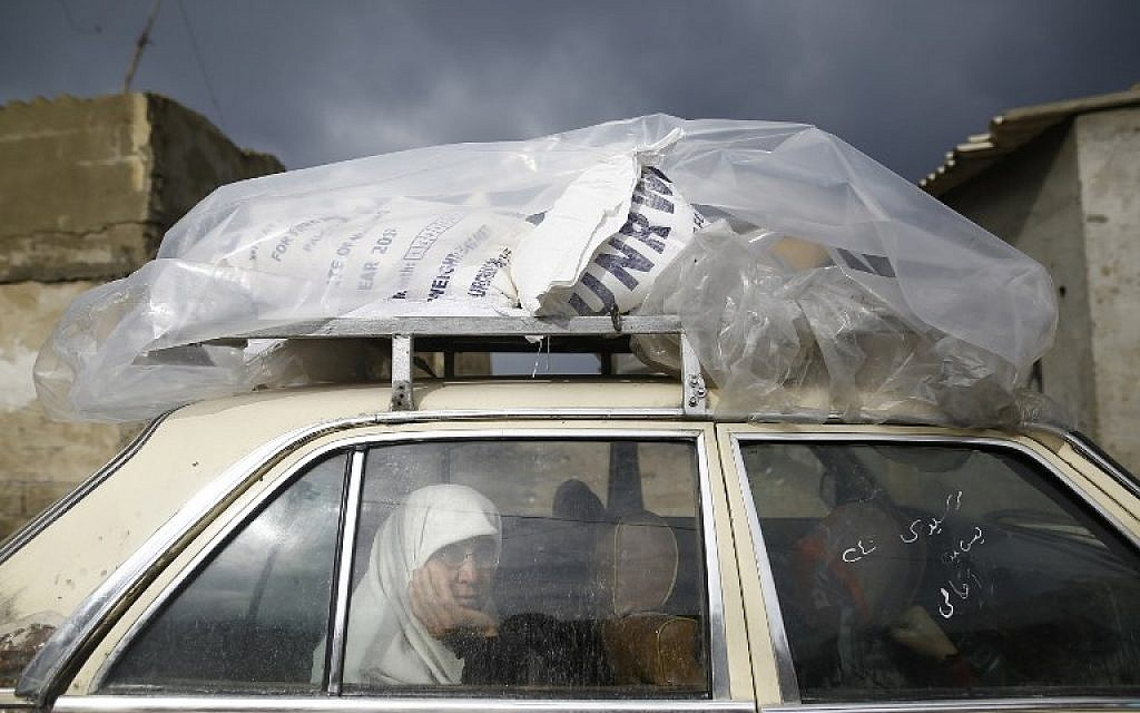 A Palestinian woman rides in a car after collecting aid provided by the UN agency for Palestinian refugees UNWRA, in Gaza City on January 17, 2018. (AFP PHOTO / MOHAMMED ABED)