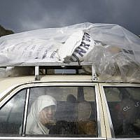A Palestinian woman rides in a car after collecting aid provided by the UN agency for Palestinian refugees UNWRA, in Gaza City on January 17, 2018. (AFP/Mohammed Abed)