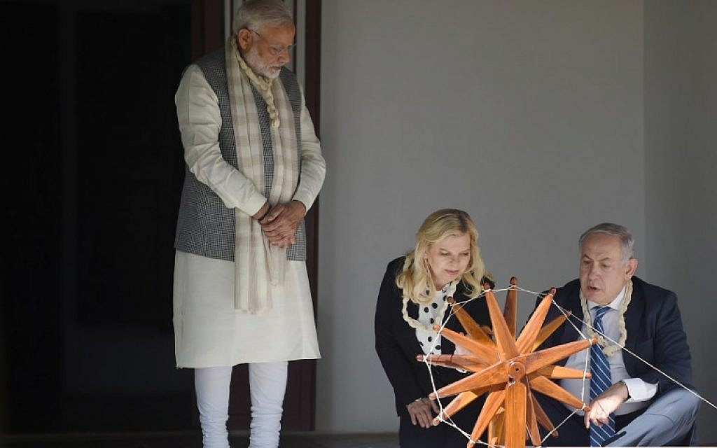 Israeli Prime Minister Benjamin Netanyahu, right, uses a spinning wheel as his wife Sara Netanyahu, center, and Indian Prime Minister Narendra Modi look on during a visit to Gandhi Ashram in Ahmedabad on January 17, 2018. AFP/SAM PANTHAKY)