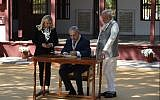 Prime Minister Benjamin Netanyahu (C) signs a visitors book as his wife Sara Netanyahu (L) and Indian Prime Minister Narendra Modi look on during a visit to the Gandhi Ashram in Ahmedabad on January 17, 2018. (AFP Photo/Sam Panthaky)