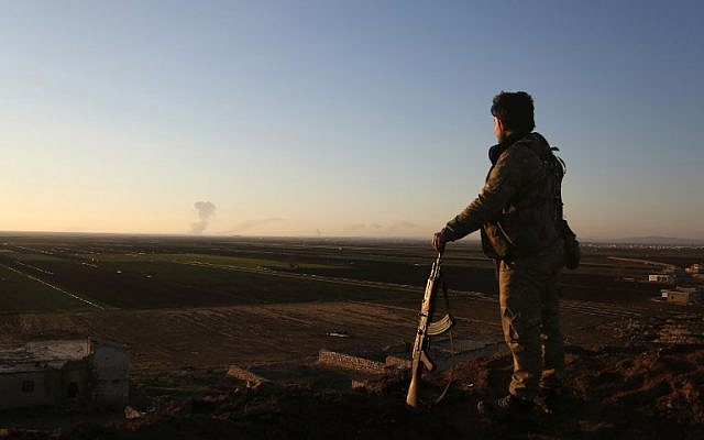 A Syrian rebel fighter stands in the Tal Malid area, north of Aleppo, as he watches smoke billow from a Kurdish People's Protection Units (YPG) position in the area of Afrin, on January 20, 2018. (AFP Photo/Nazeer al-Khatib)