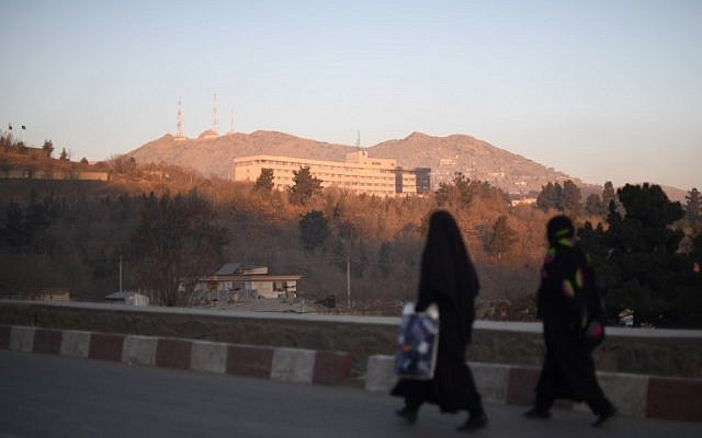 Two Afghan women walk past the Intercontinental Hotel after an attack in Kabul on January 21, 2018 (AFP PHOTO / SHAH MARAI)