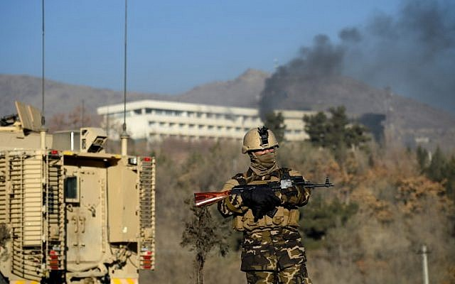 An Afghan security personnel stands guard as smoke billows from the Intercontinental Hotel during a fight between gunmen and Afghan security forces in Kabul on January 21, 2018. (AFP/ WAKIL KOHSAR)