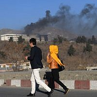 Afghans walk near the Intercontinental Hotel as smoke billows during a fight between gunmen and Afghan security forces in Kabul on January 21, 2018. (AFP PHOTO/WAKIL KOHSAR)