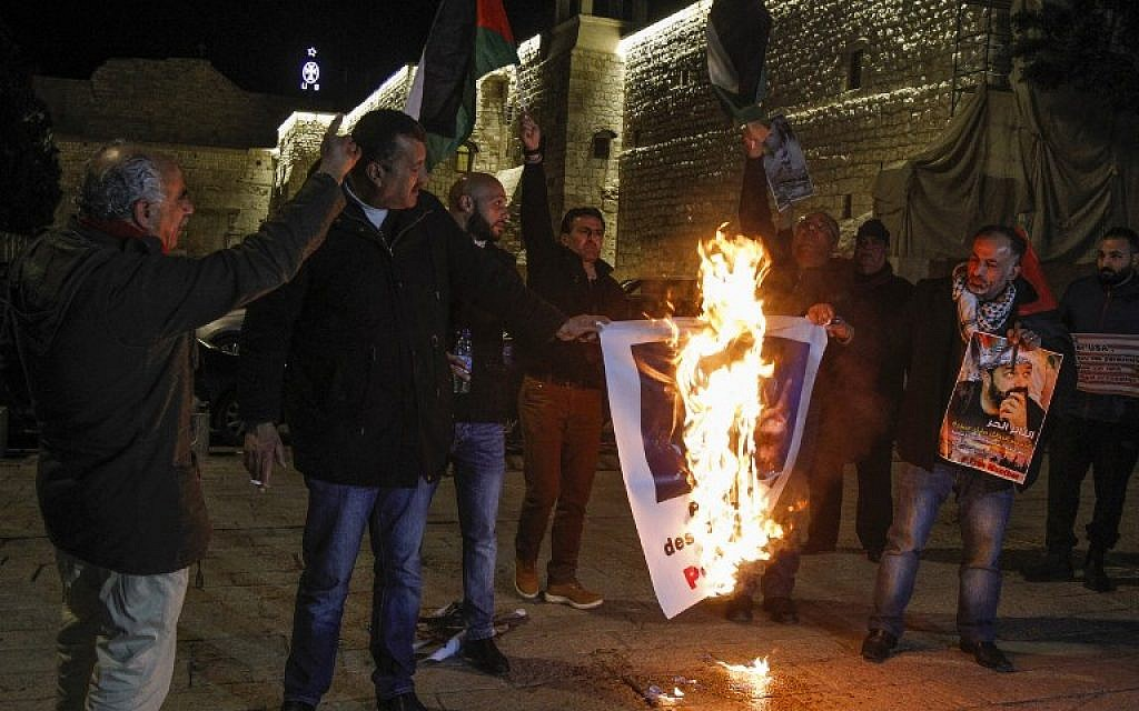 Palestinian protesters burn posters bearing portraits of US Vice President Mike Pence during a demonstration at the Manger Square in the town of Bethlehem in the occupied West Bank, on January 21, 2018. (AFP/ Musa AL SHAER)