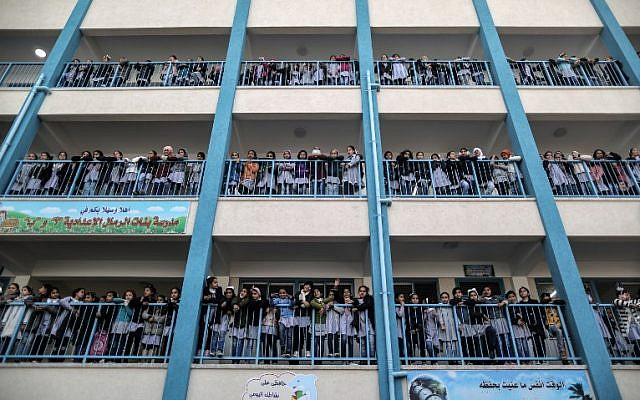 Palestinian schoolgirls pose for a group picture outside their classrooms at a school belonging to the United Nations Relief and Works Agency for Palestine Refugees (UNRWA) in Gaza City on January 22, 2018, during a visit by the UNRWA Commissioner General (AFP PHOTO / MAHMUD HAMS)