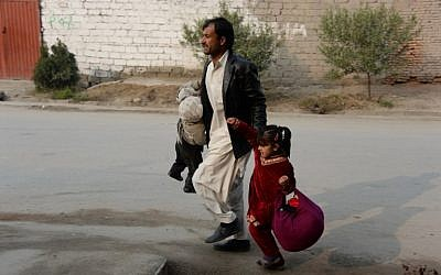 An Afghan man runs with two children near an office of the British charity Save the Children during an ongoing attack in Jalalabad on Wednesday, January 24, 2018. (AFP PHOTO/Noorullah SHIRZADA)