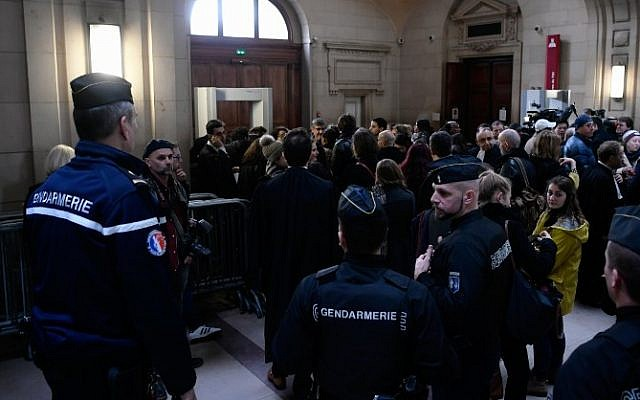 People wait outside the main courtroom ahead of the trial of Jawad Bendaoud, charged with harbouring jihadists during the November 2015 terror attacks, at the courthouse of Paris on January 24, 2018. (AFP PHOTO / Philippe LOPEZ)