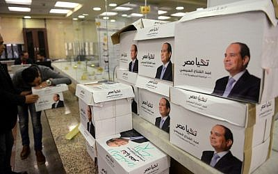 Members of Egyptian President Abdel Fattah el-Sissi's campaign staff stand next to boxes containing the signatures of support needed to register for the elections, at the National Election Authority in Cairo, on January 24, 2018. (AFP Photo/Mohamed El-Shahed)