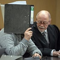 The defendant accused of a bombing at the Dusseldorf-Wehrhahn station targeting Jewish immigrants in the year 2000 hides his face behind a folder and sits next to his lawyer as he waits for the start of his trial on January 25, 2018 in Dusseldorf, western Germany. (AFP Photo/dpa/Federico Gambarini)