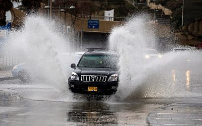 Motorists plow their vehicles through flooded streets after a winter storm hit the Israeli coastal town of Netanya, north of Tel Aviv, on January 25, 2018. (JACK GUEZ/AFP)