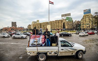 Supporters of Egyptian President Abdel Fattah al-Sissi drive a pickup truck bearing his portrait and loudspeakers, in the capital Cairo's Tahrir square on January 25, 2018. (Illustrative: AFP/ MOHAMED EL-SHAHED)