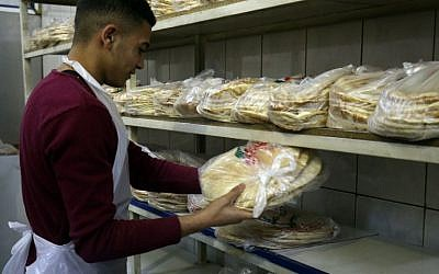A Jordanian worker packages bread at a bakery in the Jordanian capital Amman on January 27, 2018. (AFP / Khalil MAZRAAWI)
