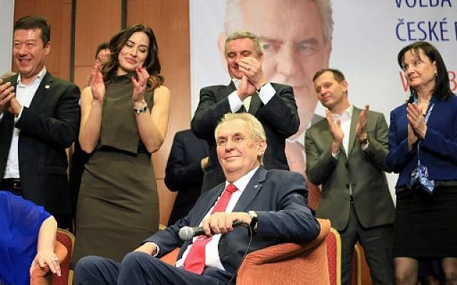 Pro-Russian incumbent Milos Zeman (seated) is applauded as he celebrates his victory with his staff members after he was reelected Czech president, January 27, 2018, at the Top hotel in Prague. (AFP / RADEK MICA)