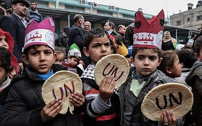 Palestinian children hold bread patties during a protest against aid cuts, outside the United Nations' offices in Khan Yunis in the southern Gaza Strip on January 28, 2018. (Said Khatib/AFP)