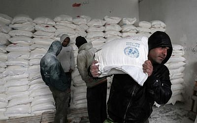 Palestinians collect food aid at a United Nations food distribution center in Khan Younis in the southern Gaza Strip on January 28, 2018. (Said Khatib/AFP)