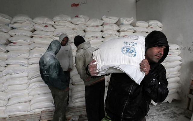 Palestinians collect food aid at a United Nations food distribution center in Khan Yunis in the southern Gaza Strip on January 28, 2018. (Said Khatib/AFP)