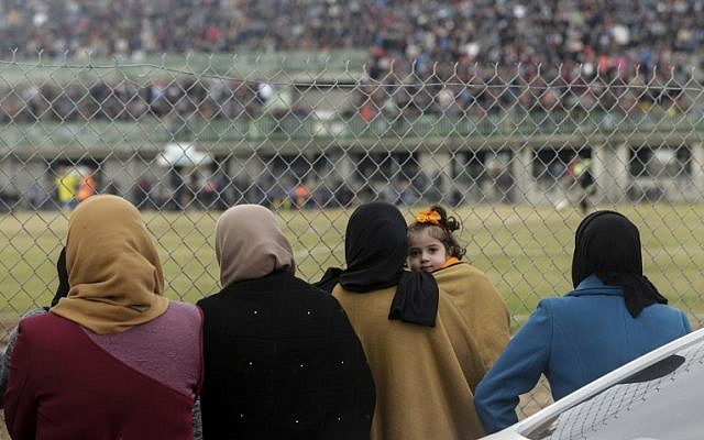 Palestinian women watch the soccer match between Al-Nuseirat and Al-Jalaa standing outside the fence of the stadium at Nuseirat refugee camp, south of Gaza City, on January 28, 2018. (AFP PHOTO / MAHMUD HAMS)