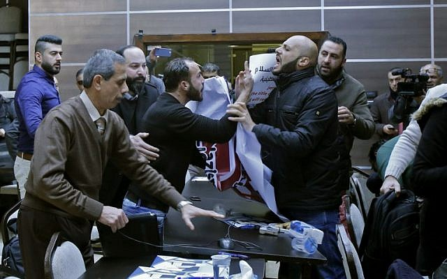 Palestinian activists disrupt a meeting between members of an American economic delegation and the Head of the Bethlehem Chamber for Commerce and Industry in the West Bank town of Bethlehem on January 30, 2018. (AFP Photo/Musa Al-Shaer)