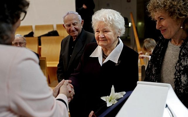 Alicja Mularska, the daughter of the late Polish couple Jan Dziadosz and Sabina Perzyna receives a medal and certificate of the Righteous Among the Nations award during a posthumous ceremony honouring her parents and their son Aleksandr Dziadosz at the Yad Vashem Museum on January 30, 2018. (AFP PHOTO / THOMAS COEX)