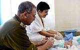 Illustrative. An IDF doctor treats a baby born with a birth defect during a humanitarian aid mission to the Philippines following a typhoon on November 18, 2013. (Israel Defense Forces/Flickr)