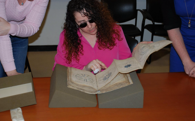 Lisa Fagin Davis, executive director of the Medieval Academy of America, reading the Voynich manuscript in 2016. (Raymond Clemens, Beinecke Rare Book and Manuscript Library)