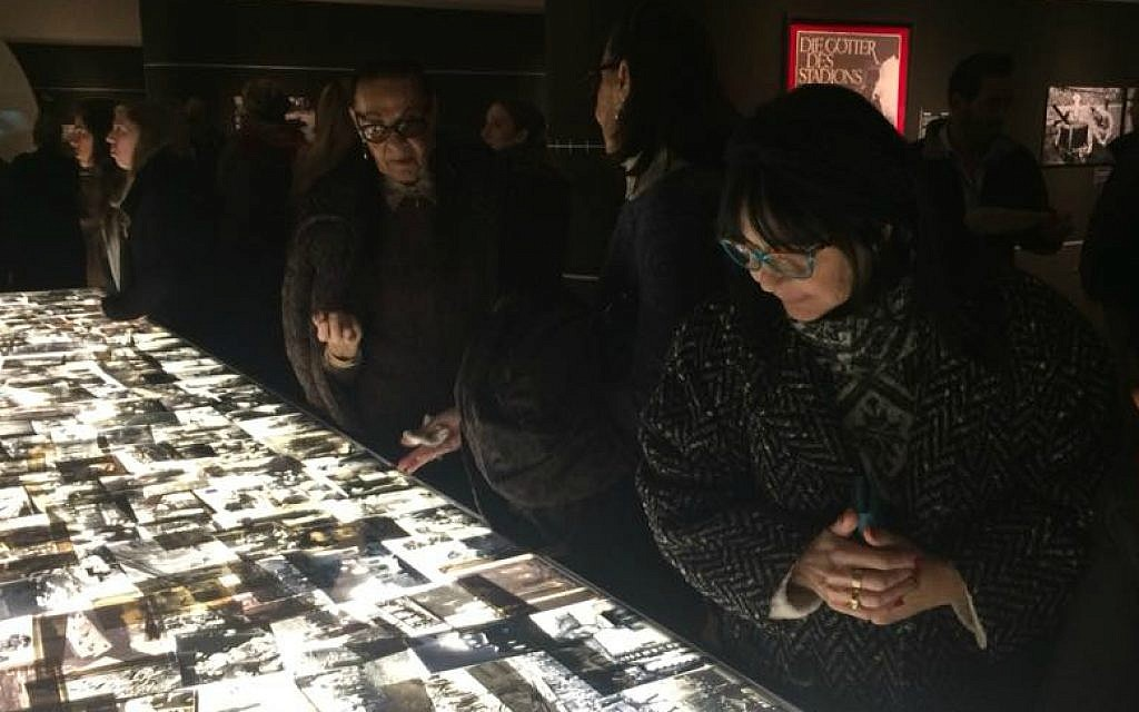 Visitors looks at hundreds of Holocaust-era images displayed on light table at opening of 'Flashes of Memory' exhibition at Yad Vashem, January 24, 2018 (Renee Ghert-Zand/TOI)