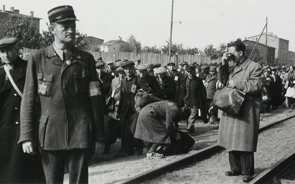 Łódź ghetto photographer Mendel Grossman clandestinely photographing the deportation of Jews. The photo was taken by Grossman's assistant, Aryeh Ben-Menachem. (Yad Vashem Archives)