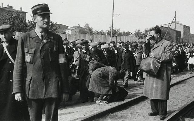Łódź ghetto photographer Mendel Grossman clandestinely photographing the deportation of Jews from the Łódź ghetto. The photo was taken by Grossman's assistant, Aryeh Ben-Menachem. (Yad Vashem Archives)