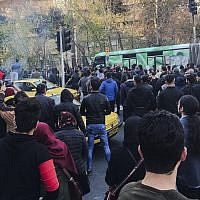 University students attend a protest inside Tehran University while a smoke grenade is thrown by anti-riot Iranian police, in Tehran, Iran, December 30, 2017. (AP Photo)
