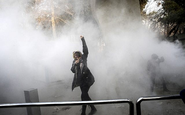 University students attend an anti-regime protest inside Tehran University while a smoke grenade is thrown by Iranian anti-riot police, in Tehran, Iran, December 30, 2017. (AP Photo)