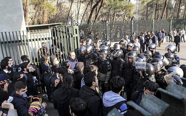 University students attend a protest inside Tehran University while a smoke grenade is thrown by Iranian anti-riot police, Tehran, Iran, December 30, 2017. (AP Photo)