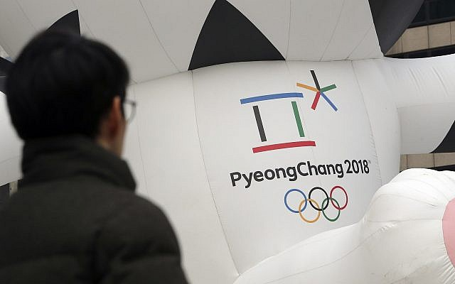 A man walks by the official emblem of the 2018 Pyeongchang Olympic Winter Games, in downtown Seoul, South Korea, December 29, 2017. (AP Photo/Lee Jin-man)