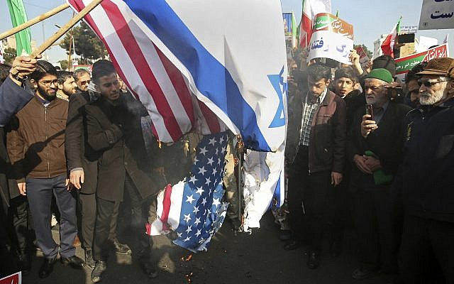 In this photo provided by Tasnim News Agency, Iranian demonstrators burn representations of US and Israeli flags in a pro-government rally in the northeastern city of Mashhad, Iran, Thursday, Jan. 4, 2018. (Nima Najafzadeh,Tasnim News Agency via AP)