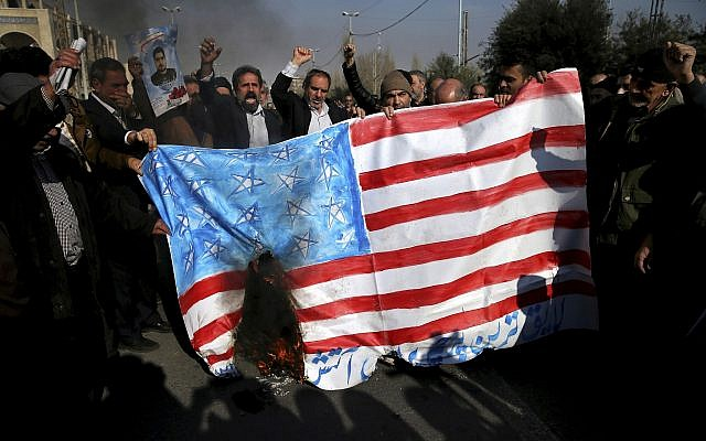 Iranian worshippers chant slogans while they burn a representation of US flag during a rally against anti-government protestors after the Friday prayer ceremony in Tehran, Iran, January 5, 2018. (AP Photo/Ebrahim Noroozi)
