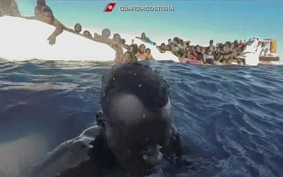This frame of a video taken by the Italian Coast Guard on January 6, 2018, in the Mediterranean Sea off Libya, shows migrants being rescued from dinghies as they try to cross to Italy. (Italian Coast Guard via AP Photo)