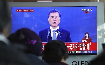 People watch a live broadcast of South Korean President Moon Jae-in's New Year's speech at the Seoul Railway Station in Seoul, South Korea, Wednesday, Jan. 10, 2018. (AP Photo/Lee Jin-man)