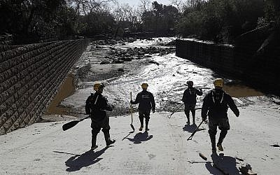 Members of the Los Angeles County Fire Department Search and Rescue crew walk toward flooded waters in Montecito, California, on Wednesday, January 10, 2018. (AP/Marcio Jose Sanchez)