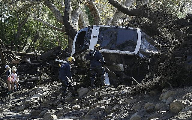 Members of the Los Angeles County Fire Department Search and Rescue crew work on a car trapped under debris in Montecito, Calif., Wednesday, Jan. 10, 2018. Dozens of homes were swept away or heavily damaged and several people were killed Tuesday as downpours sent mud and boulders roaring down hills stripped of vegetation by a gigantic wildfire that raged in Southern California last month. (AP Photo/Marcio Jose Sanchez)
