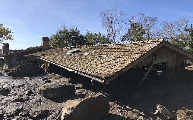 In this photo provided by Santa Barbara County Fire Department, mudflow, boulders, and debris from heavy rain runoff from early Tuesday reached the roof of a single story home in Montecito, Calif., on Wednesday, Jan. 10, 2018. A storm caused deadly mudslides in fire-scarred areas of Montecito and adjacent Santa Barbara County. (Mike Eliason/Santa Barbara County Fire Department via AP)