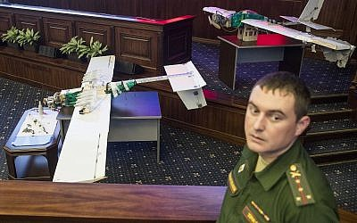 A Russian officer stands next to drones that attacked the Russian air base in Syria and were captured by the Russian military are displayed at a briefing in the Russian Defense Ministry in Moscow, Russia, Thursday, Jan. 11, 2018. (AP Photo/Pavel Golovkin)