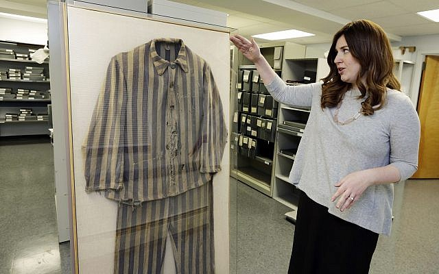 Shoshana Greenwald, director of Collections  at the Amud Aish Memorial Museum, in Brooklyn, NY, talks about the 1945 uniform of Bergen-Belsen concentration camp survivor Chaim Schmidt, in the museum's archive room, on January 10, 2018. (AP Photo/ Richard Drew)