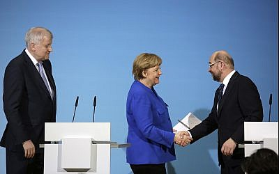 German Chancellor Angela Merkel, center, shakes hand with Social Democratic Party Chairman Martin Schulz as Bavarian governor Horst Seehofer, left, looks on during a joint statement after the exploratory talks between Merkel's Christian Democratic block and the Social Democrats on forming a new German government in Berlin, Germany, on January 12, 2018. (AP Photo/Markus Schreiber)