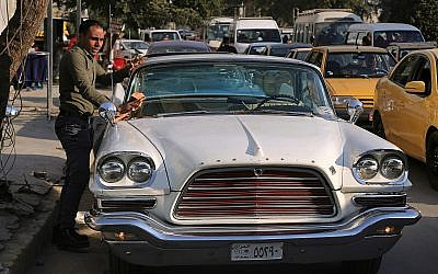 In this Wednesday, January 10, 2018 photo, a man cleans a 1952 Chrysler parked in front of owner Saad al-Nuaimi's coffee shop in the northern Azamiyah neighborhood of Baghdad, Iraq. (AP Photo/Khalid Mohammed)