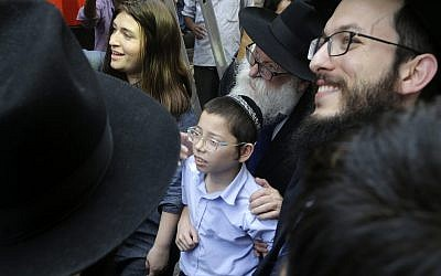 Moshe Holtzberg, center, a young boy whose parents were killed at the Chabad House in Mumbai during a 2008 terror attack, arrives with grandparents at the site of the attack on Tuesday, January 16, 2018 (AP Photo/Rajanish Kakade)